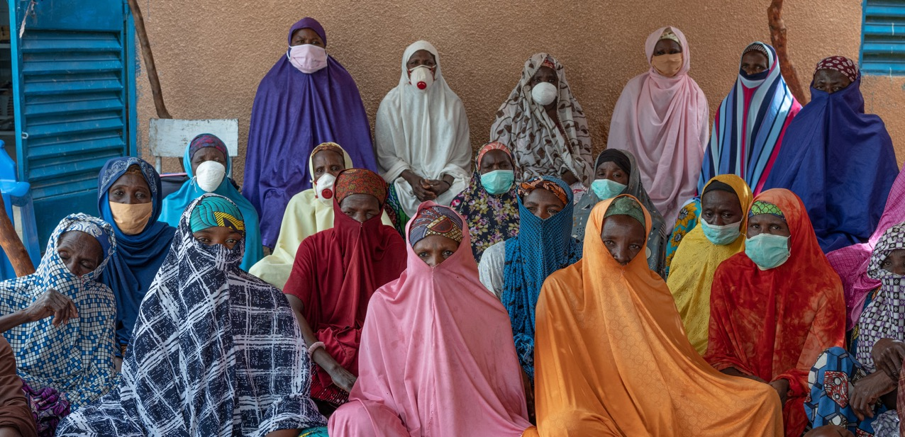 Group of women sitting together wearing face masks