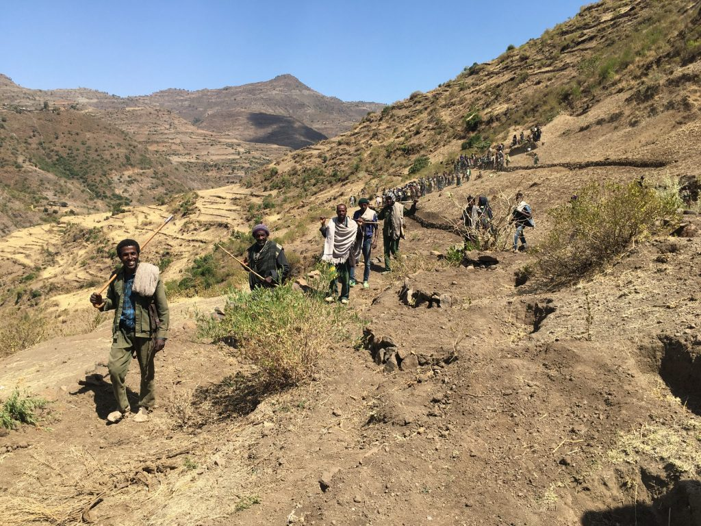 A group of people walking up a hillside in Ethiopia