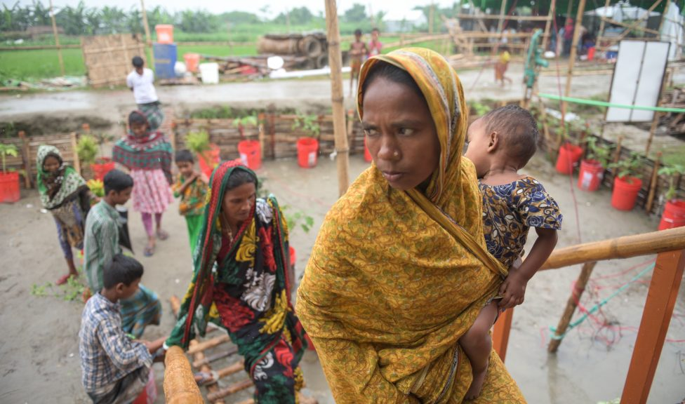 Women carrying a child walking up stairs to a floating house in Bangladesh.