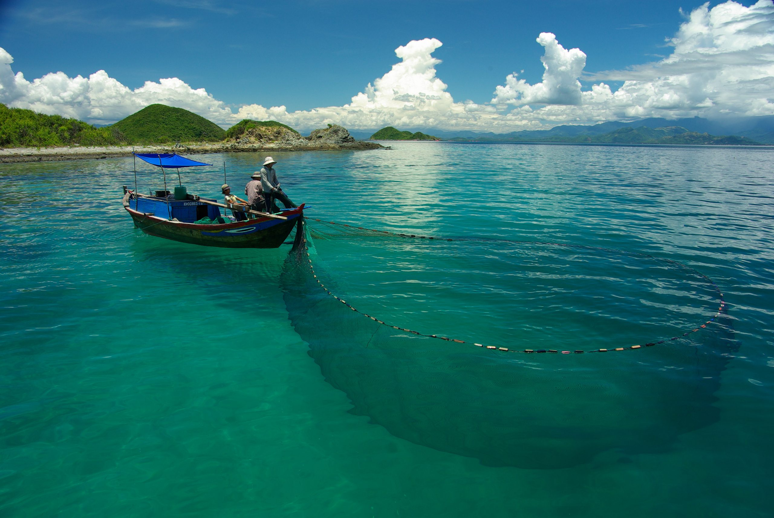 A small fishing boat and fishermen fish using a net.