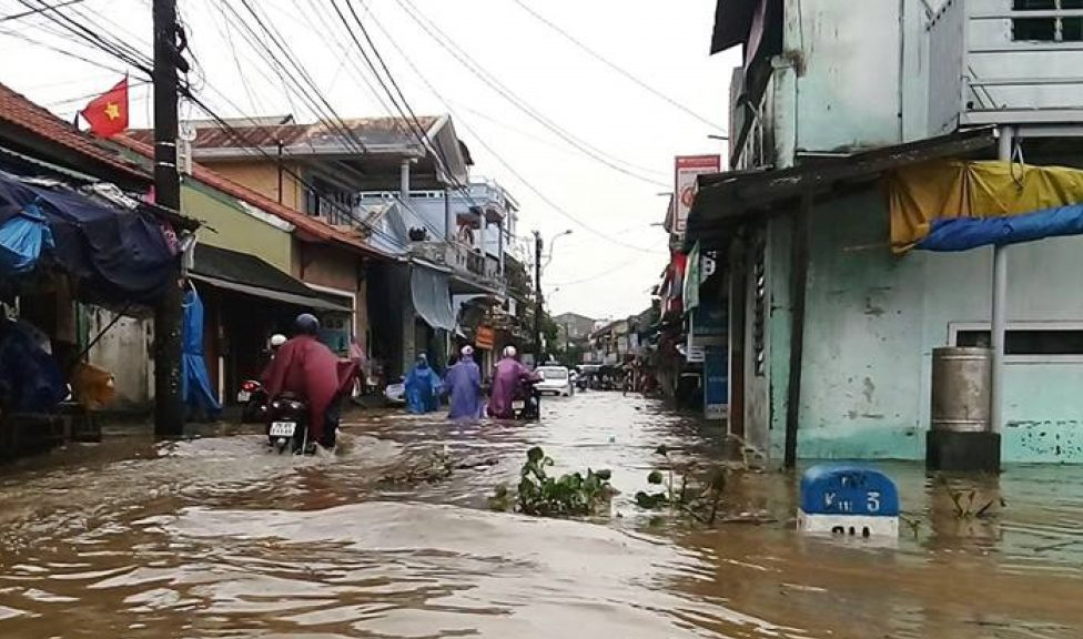 Flooded road in Vietnam with people trying to get through on motorbikes.