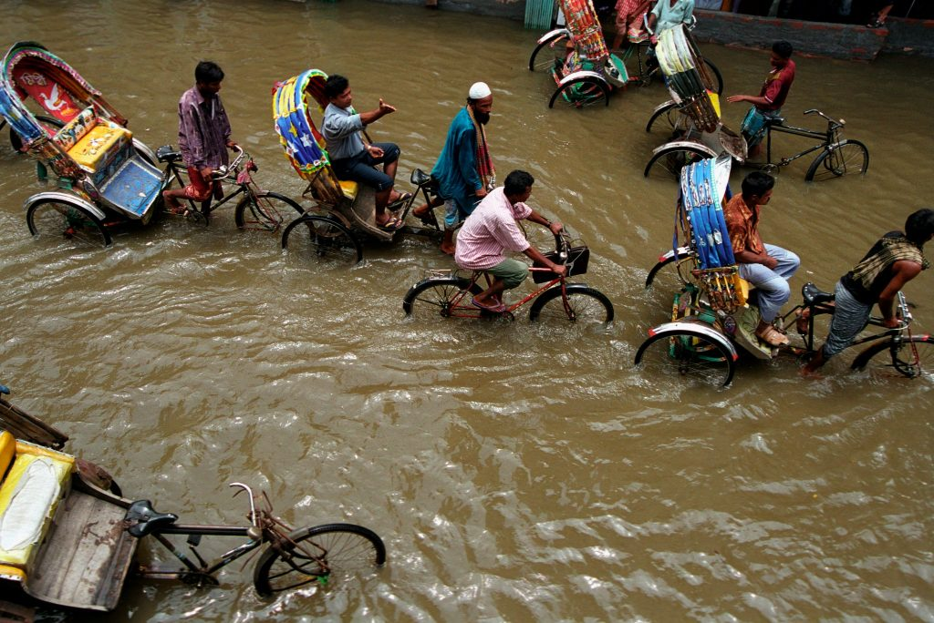 People biking through a flooded street