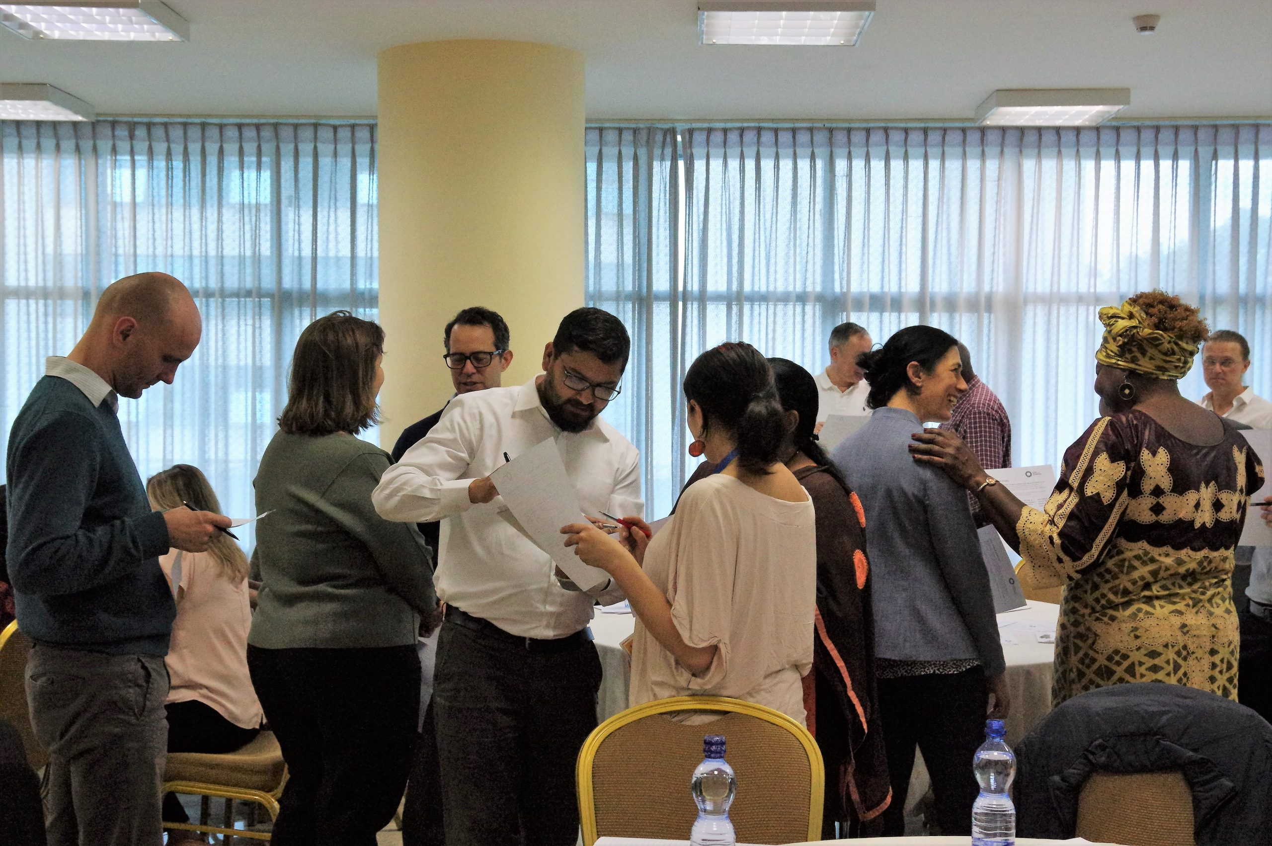A group of people talking to each other and filling out a form together.