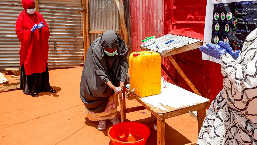 Women with a mask on filling up water from a jug.