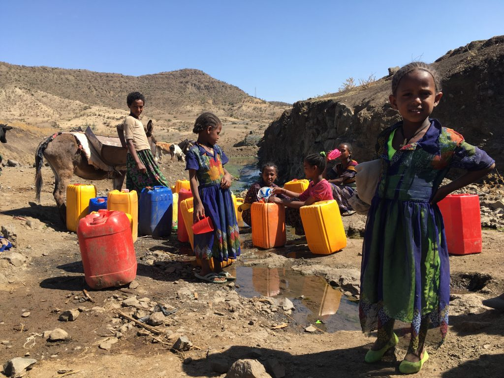 Children collecting water from a spring in Ethiopia