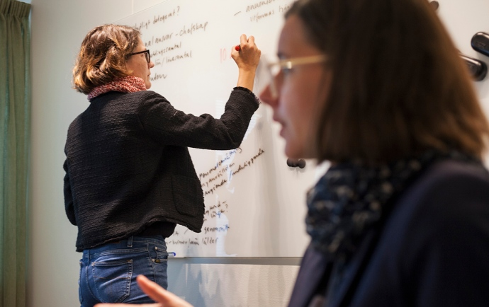 A women is writing on a whiteboard, while another one is talking.